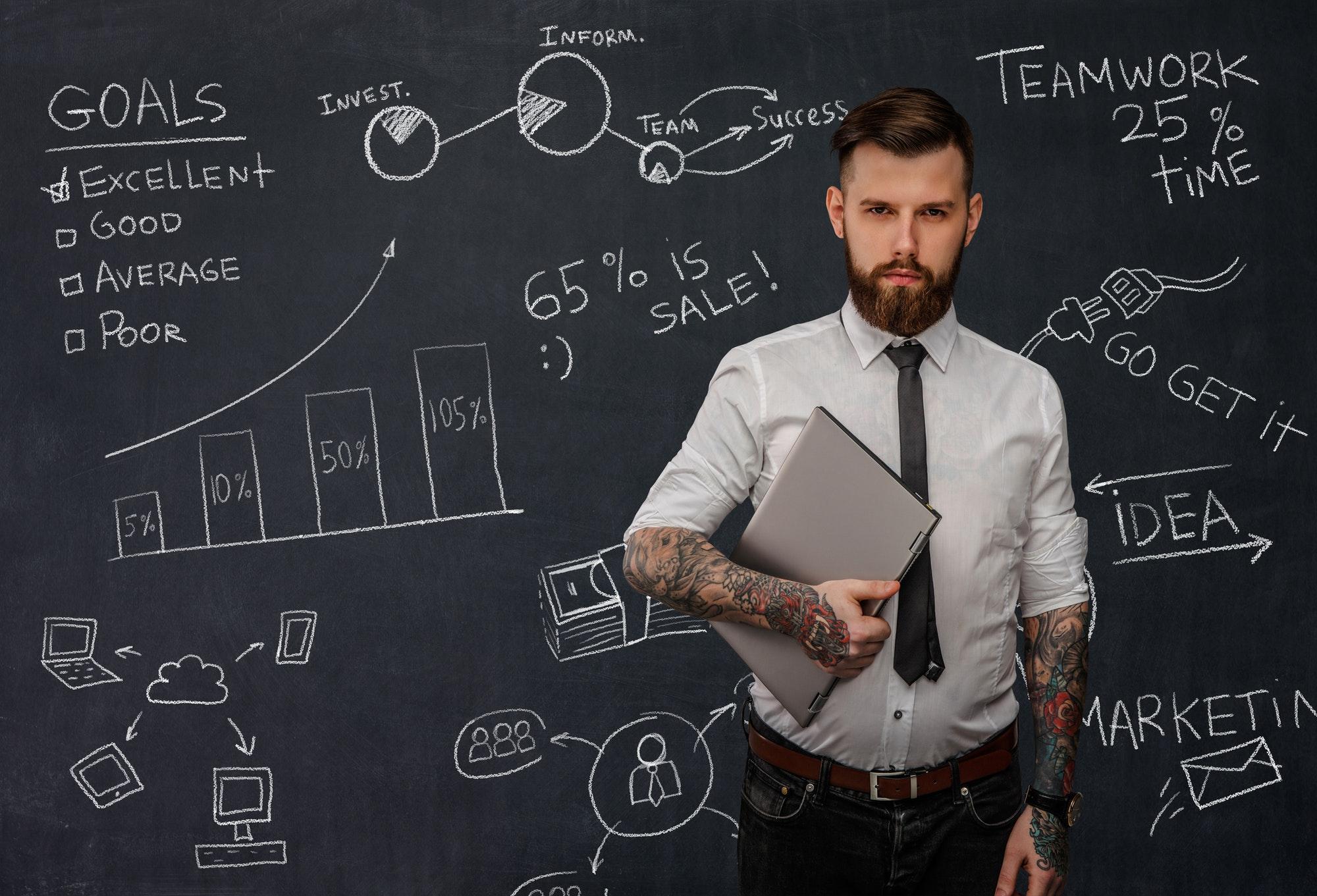 Tattooed bearded techer with laptop.